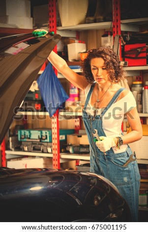 Owner of a car repair shop, a beautiful woman in a jeans jumpsuit of a car mechanic opened the bonnet cover and looks at the engine. instagram image filter retro style