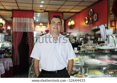 owner of a small business/ cake store/ cafe showing her tasty cakes - stock photo