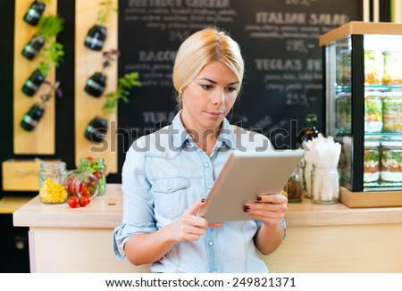 Owner of small restaurant holding a digital tablet - stock photo