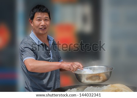 Owner of small restaurant prepares rice in the street in city Shangri-La. - stock photo