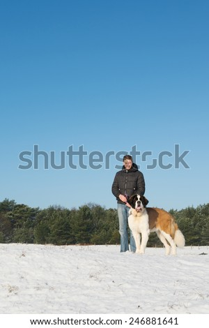 Owner with big rescue dog in snow - stock photo