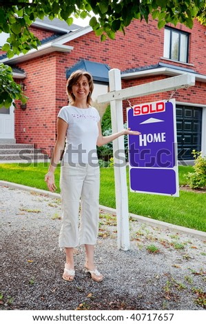 Owner with Home Sold Sign in front of a house in a modern suburban neighborhood