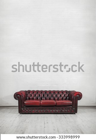 oxblood red vintage sofa against painted brick wall (place text or canvas on wall)
