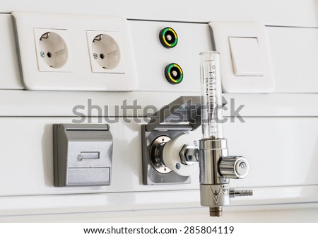 Oxygen flow meter suply, named Thorpe tube, for respirator regulation in a brightly lit hospital room at treatment end. Natural sunlight gives a positive feeling of patient's successful full recovery. - stock photo