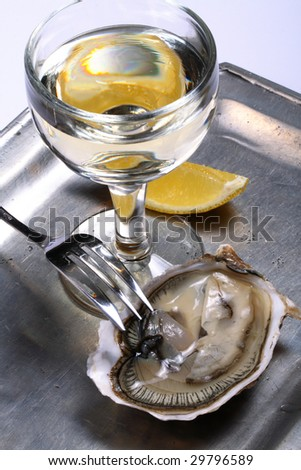 Oyster, a glass of white wine and lemon on a silver tray