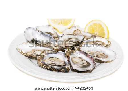 Oyster and lemon on white background On white plate - stock photo