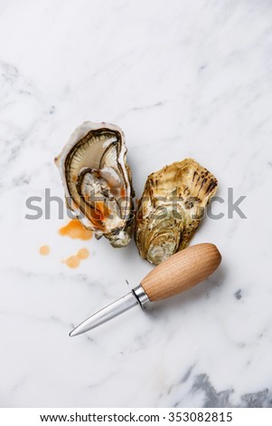 Oyster and oyster knife on white marble background with spicy sauce - stock photo