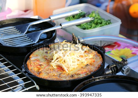 Oysters fried in egg batter on iron pan (cooking) - Thailand food Pan-fried crispy mussel with bean sprout, Crisp fried oyster pancake - (Hoi Tod) - stock photo