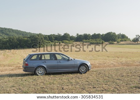 ozlets, Bulgaria - July 30, 2015: BMW 3 Series E46 in a wheat bales field. The BMW E46 is the fourth generation of the 3 Series compact executive cars, produced by BMW. It was produced from 1998.