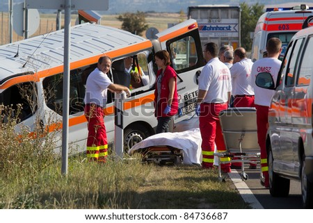 PÉCS, HUNGARY - SEP 15: Firefighters help the victim of car accident on Sept. 15, 2011 on Road 6 in Pécs, Hungary. - stock photo