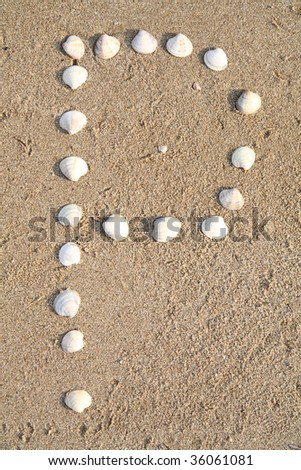 p letter symbol created from shells on a beach sand