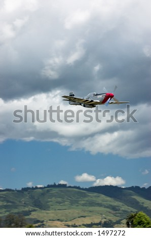 P-51 Mustang flying under clouds