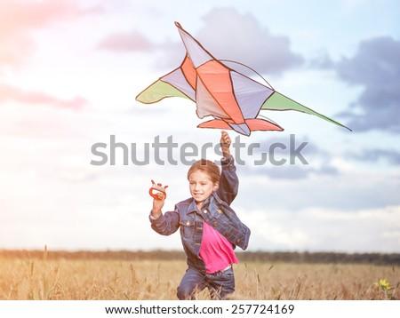 p[retty little girl flies a kite in a field of wheat - stock photo