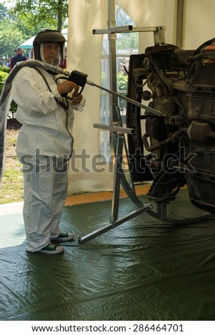 PAAREN IM GLIEN, GERMANY - MAY 23, 2015: Repairman demonstrates the device for cleaning the car body against corrosion. The oldtimer show in MAFZ.