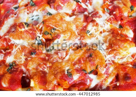 Paccheri baked with tomato sauce, mozzarella, bacon and basil. Italian culinary specialties. View from above.