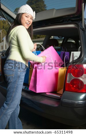 Pacific Islander woman putting shopping bags into car