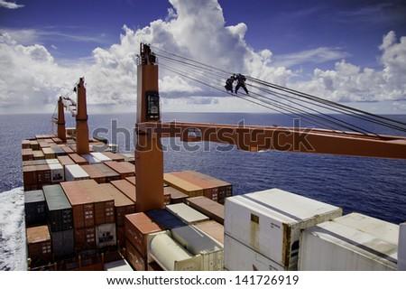 PACIFIC OCEAN - DECEMBER 4, 2008. Seamen grease steel wire of container ship's crane. Pacific Ocean on December 4. - stock photo