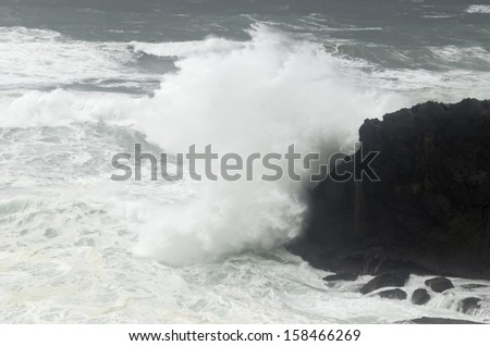 Pacific Ocean wave crashing against dark volcanic rock along the Oregon coast - stock photo