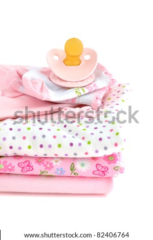 Pacifier and a pile of pink baby clothes, isolated on white - stock photo