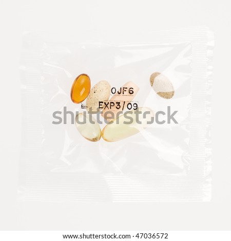 Pack of daily vitamin supplements in a clear plastic bag, stamped with an expiration date. Square format. Isolated on white. - stock photo