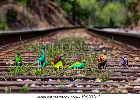 Pack of dinosaurs walking on railroad tracks