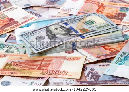 Pack of dollars against the background of paper Russian money. Type acute angle