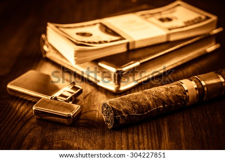 Pack of dollars and golden lighter with a leather diary and cuban cigar on a mahogany table. Shallow depth of field, focus on the cuban cigar, image vignetting and yellow-orange toning - stock photo
