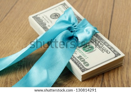 Pack of dollars in a blue ribbon on wooden background