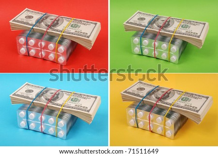 Pack of dollars lays on packing of white tablets. On four green, red, blue, yellow background.