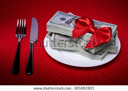 Pack of dollars on a plate, cutlery on the tablecloth, red bow of the braid, economic concept, serving business lunch, a red tablecloth in a black polka dots.
