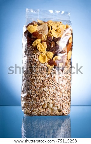 Pack of muesli (Dry breakfast, mixture of corn flakes and dried fruit) on a blue background - stock photo