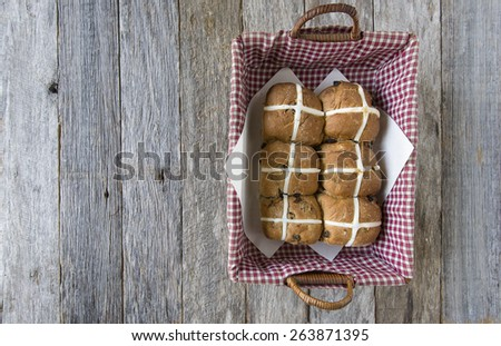 pack of six easter hot cross buns in red checked basket on rustic wooden background - stock photo