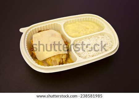 Package for freezing food or to go of parmesan chicken fillet, rice and mashed potatoes on brown background. - stock photo
