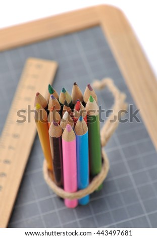 package of colored pencils with wooden rule on a slate  - stock photo