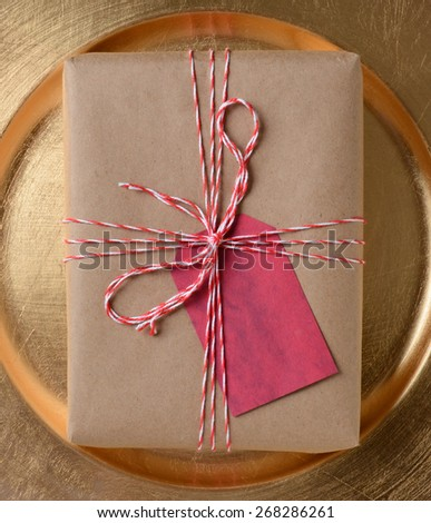 Package on a gold platter, The gift is wrapped in plain brown paper and tied with red and white twine. A blank red gift tag is attached to the present. - stock photo