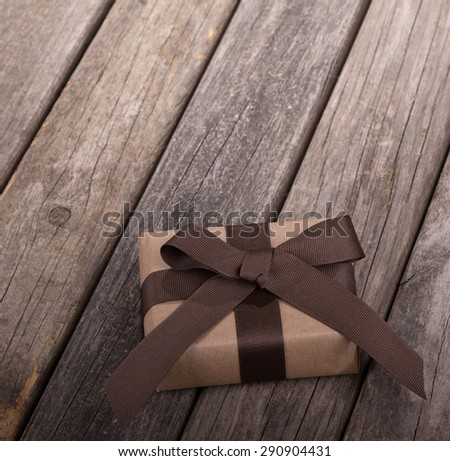 Package wrapped in brown ribbon and bow on old wood boards - stock photo
