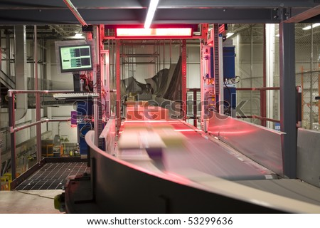 Packages being scanned and distributed on conveyor belt - stock photo