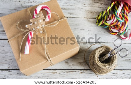 Packed Christmas cardboard with candy cane on top. Horizontal studio shot
