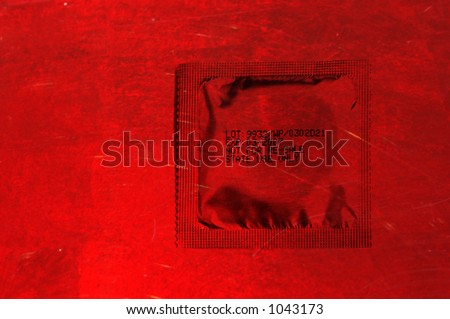 packed condom over a red background - stock photo