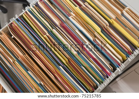 Packed file cabinet with colorful hanging file folders.