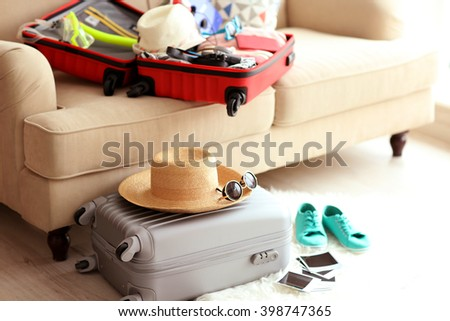 Packed grey suitcase on the floor, close up - stock photo