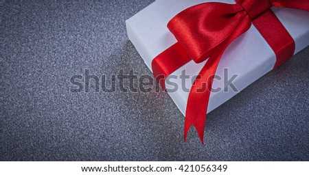 Packed present box with red bow on grey surface holidays concept. - stock photo