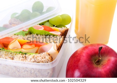 Packed sandwich with fruit and orange juice - stock photo