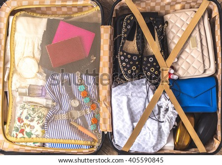 Packed suitcase of vacation items - stock photo