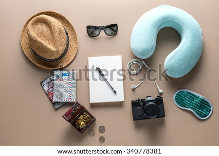 """Packed suitcase of vacation items on wooden table, top view. Eye mask with the inscription """"Wake me up for meal"""", different languages. - stock photo"""