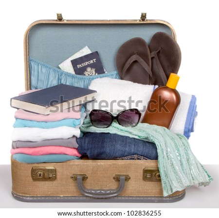 Packed vintage suitcase full of vacation items - stock photo