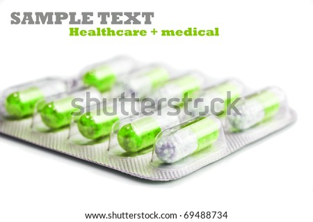 Packet of green and white capsules in a white background with space for text - stock photo