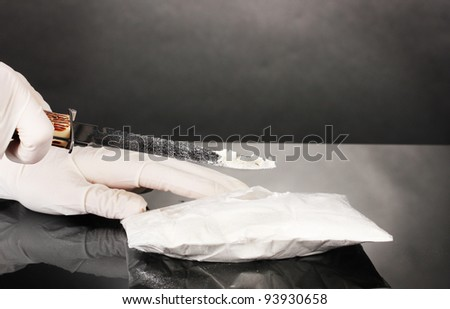 packets of Cocaine opening with a knife on grey background