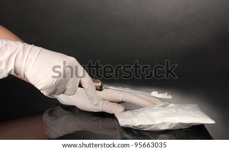 packets of Cocaine opening with a knife on grey background - stock photo