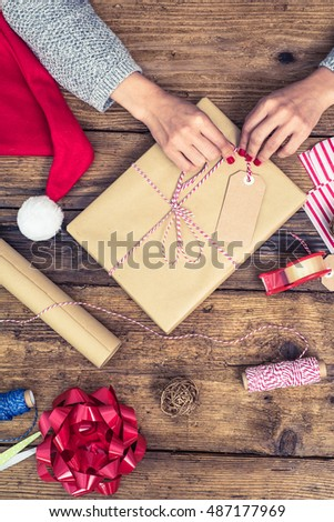 stock photo packing christmas and new year gift woman hands with red nails overhead view 487177969